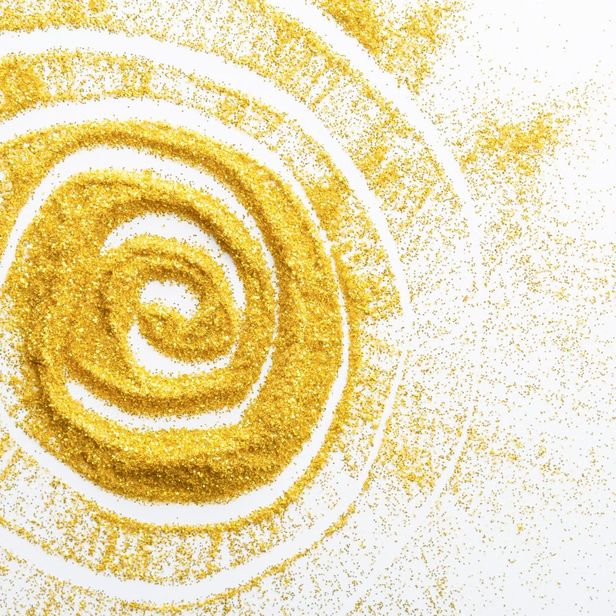 Sand painting concept. Golden glitter sand texture spread over white surface with sun shape, abstract background, top view. Yellow dusty shimmer decoration, shiny and sparkling.
